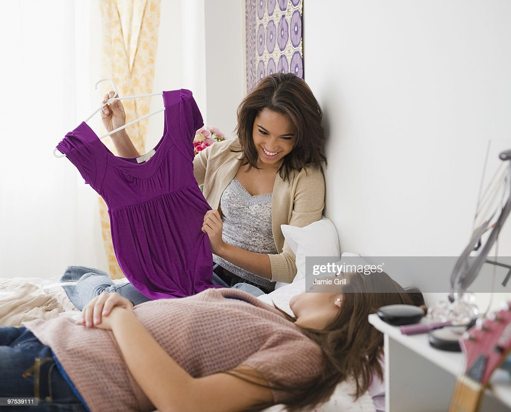 Teenage girl showing new shirt to friend : Stock Photo