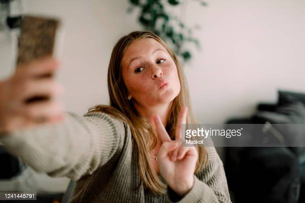 teenage girl showing peace sign while taking selfie through mobile phone at home - puckering stock pictures, royalty-free photos & images