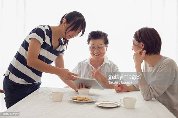 Teenage girl showing tablet to mother and grandmother