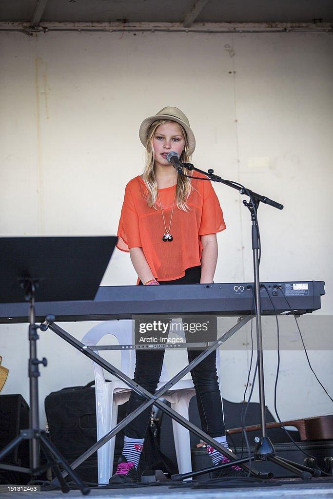 Teenage girl singing and playing keyboards : Stock Photo