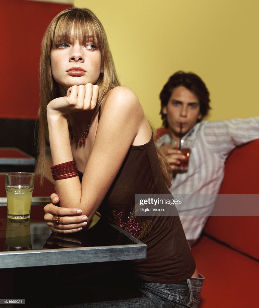 Teenage Girl Sits Leaning Her Elbow On A Table Ignoring The Man Sitting Behind Her On A Leather