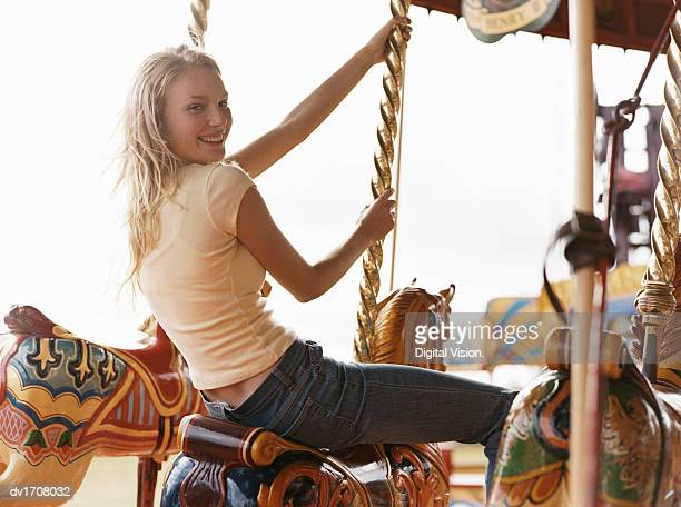 Teenage Girl Sits on a Carousel Horse, Looking Over Her Shoulder at the Camera and Smiling