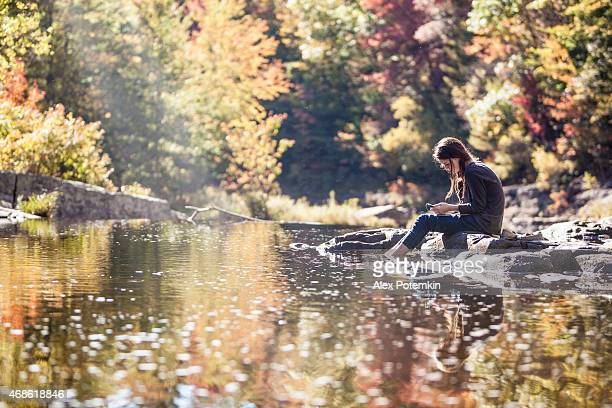 Teenage girl sits on a rock at the river using her phone