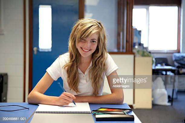 'Teenage girl (14-16) sitting at desk drawing in sketchbook, portrait'