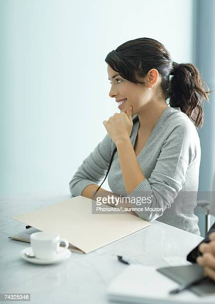 Teenage girl sitting at table with file and coffee cup, side view