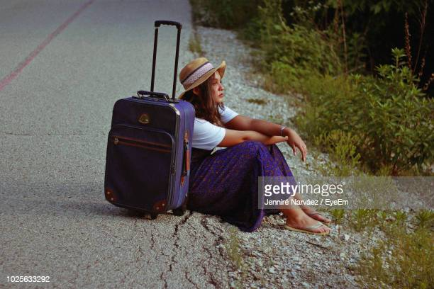 teenage girl sitting by wheeled luggage on road - wheeled luggage stock photos and pictures