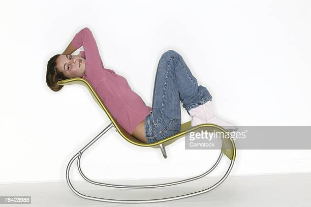 Teenage girl sitting in contemporary rocking chair