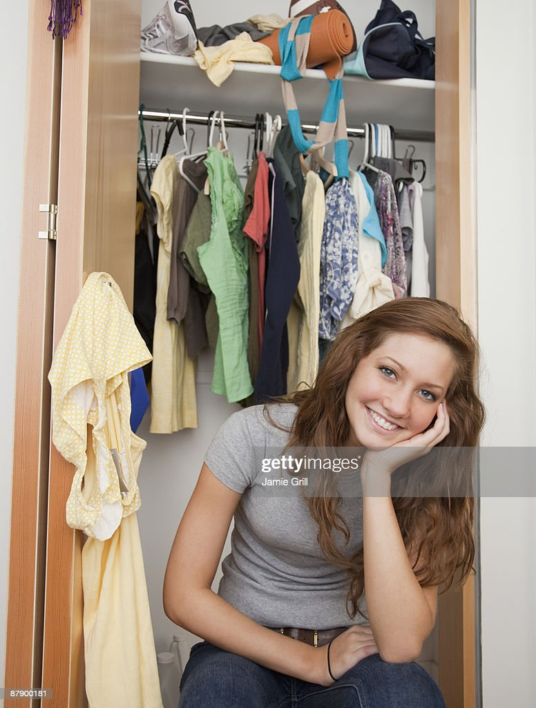 Teenage Girl Sitting In Front Of Bedroom Closet : Stock Photo