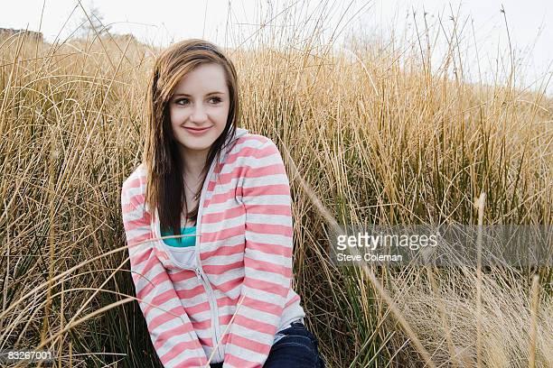 Teenage girl sitting in grassy field