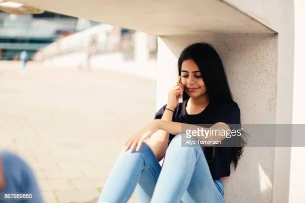 Teenage girl sitting in urban setting, using mobile phone