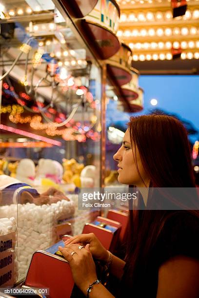teenage girl sitting infront of slot machine in casino, side view - teen pokies stock photos and pictures