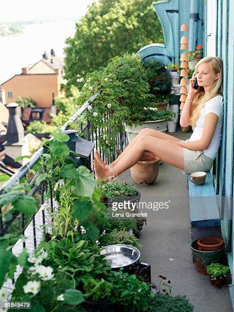 A teenage girl sitting on a balcony talking in the phone Sweden.