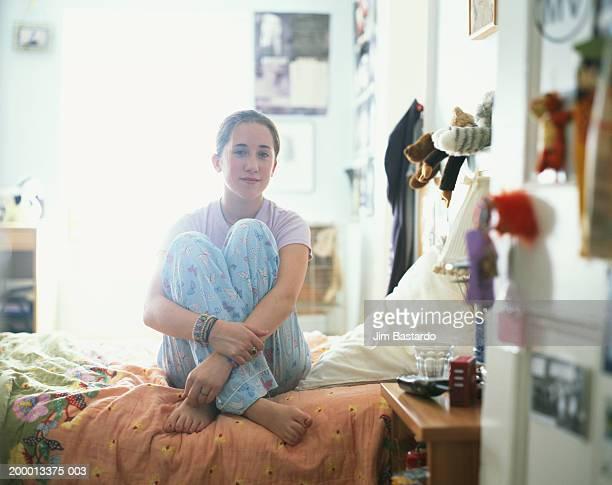 Teenage girl (12-14) sitting on bed, portrait