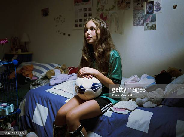 teenage girl (12-14) sitting on bed with soccer ball - traje de fútbol fotografías e imágenes de stock
