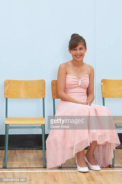 Teenage girl (12-14) sitting on chair at dance in school gymnasium