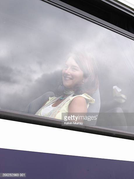 Teenage girl (16-18) sitting on coach, smiling, view through window