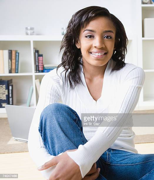 teenage girl (16-17) sitting on desk in front of shelves - one teenage girl only stock pictures, royalty-free photos & images
