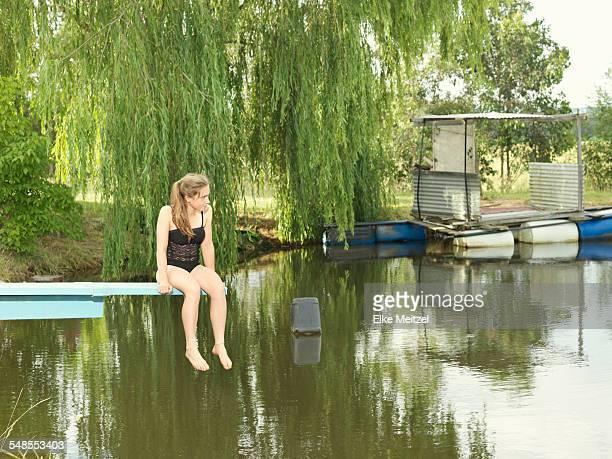 Teenage girl sitting on diving board over lake