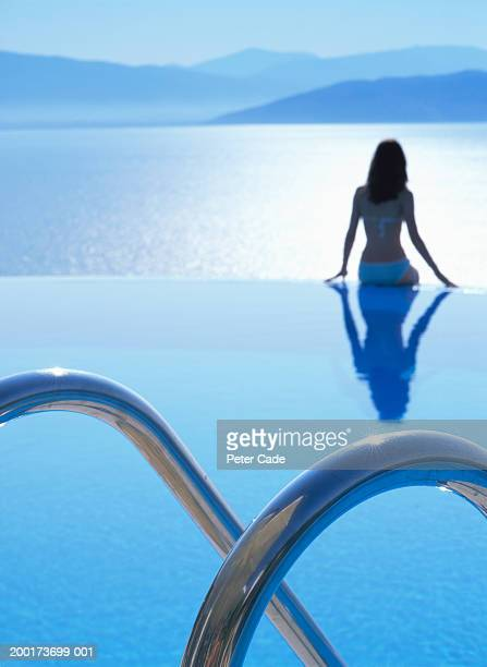 teenage girl (15-17) sitting on edge of infinity pool, rear view - travel14 stock pictures, royalty-free photos & images