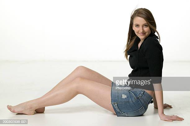 Teenage girl (16-17) sitting on floor in studio, portrait