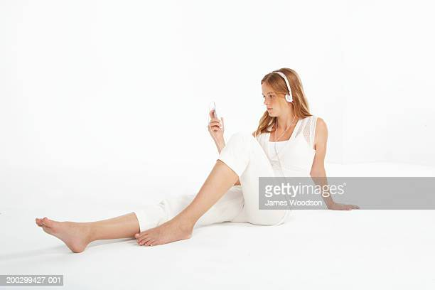 teenage girl (13-15) sitting on floor looking at personal stereo - one teenage girl only stock pictures, royalty-free photos & images