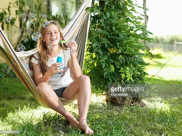 Teenage girl sitting on hammock, blowing bubbles