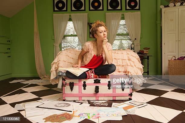 Teenage girl sitting on ottoman with drawings on bedroom floor
