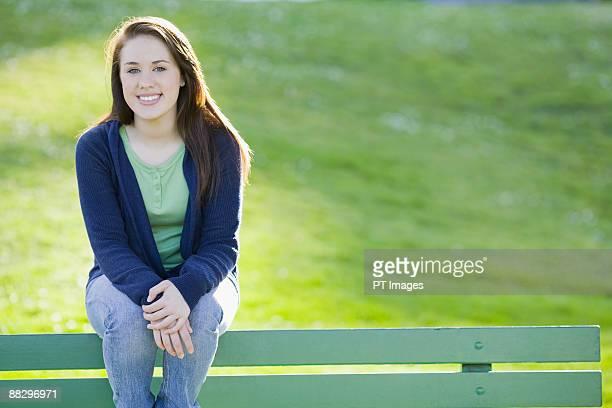 teenage girl sitting on park bench - une seule adolescente photos et images de collection