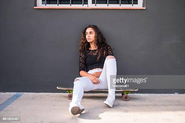 teenage girl sitting on skateboard - une seule adolescente photos et images de collection