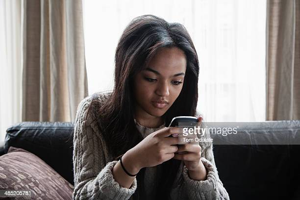 Teenage girl sitting on sofa texting on smartphone