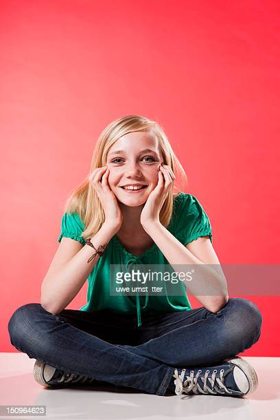 Teenage girl sitting on the floor and smiling