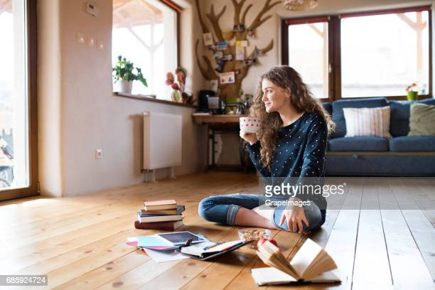 teenage girl sitting on the floor holding cup of coffee, studying - ragazzine scalze foto e immagini stock