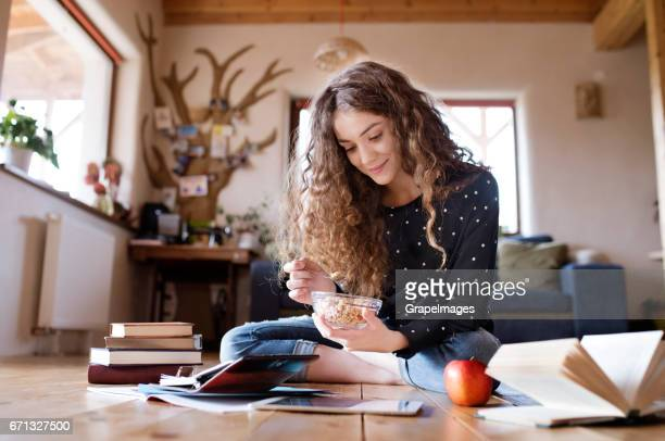 teenage girl sitting on the floor, studying, eating granola - nut food stock photos and pictures