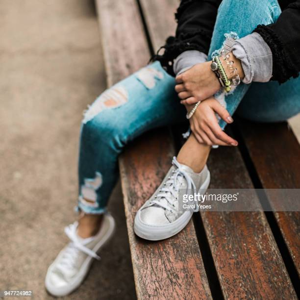 teenage girl sitting on the park bench in denim  jeans sneakers - hands in her pants - fotografias e filmes do acervo