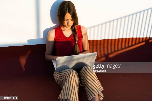 teenage girl sitting outdoors in sunlight using laptop - red pants stock pictures, royalty-free photos & images
