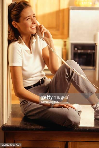 Teenage girl (16-17 years) sitting, talking on phone in kitchen