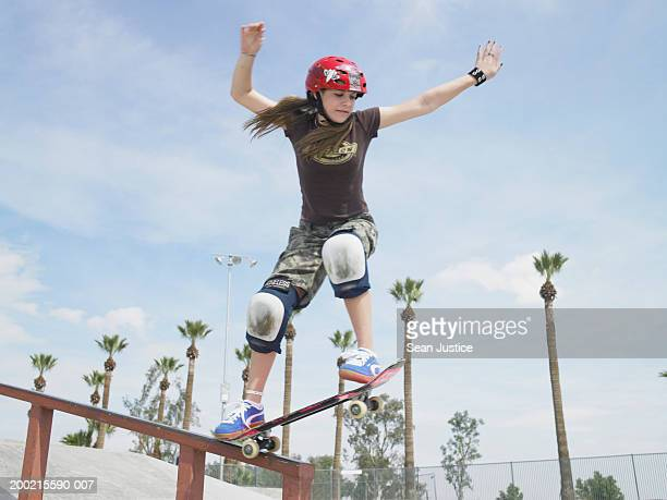 Teenage girl (14-16) skateboarding down rail