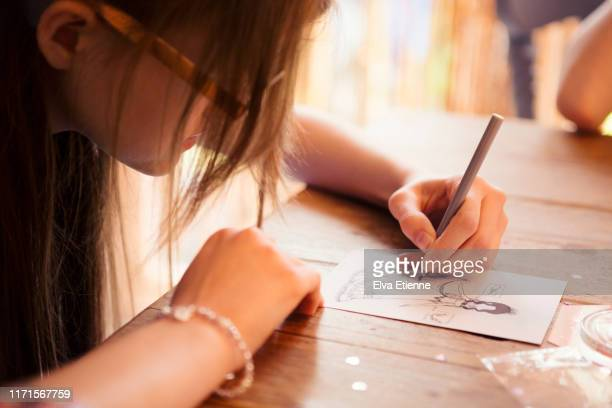 teenage girl sketching a fashion design on a peice of paper at a dining table - drawing stock pictures, royalty-free photos & images