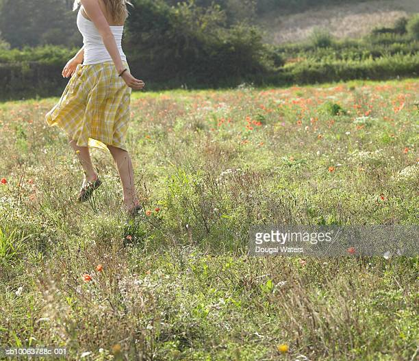 Teenage girl (16-17) skipping in meadow, rear view