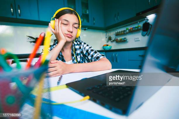 teenage girl sleeping during online class in front of laptop - distante foto e immagini stock