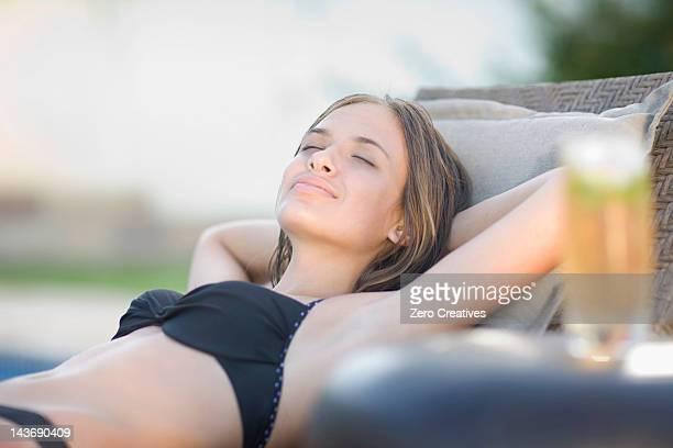adolescente ragazza di dormire in sedia da giardino - solo bambine femmine costume da bagno foto e immagini stock