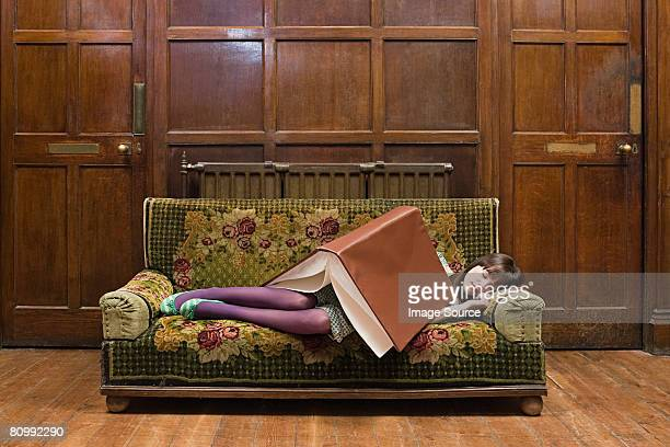 a teenage girl sleeping with a large book on her - groot stockfoto's en -beelden