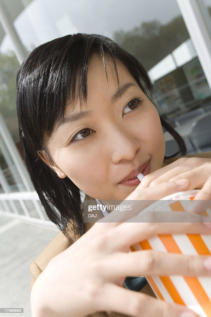 Teenage girl smiling and drinking at terrace : Photo