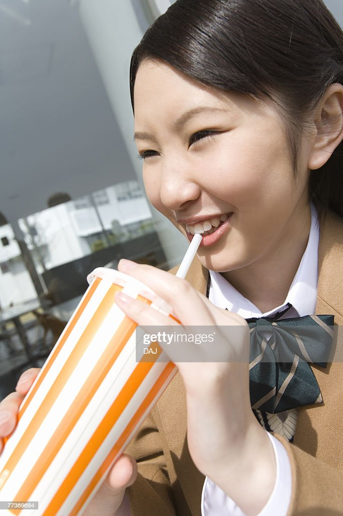 Teenage girl smiling and drinking at terrace : Stock Photo