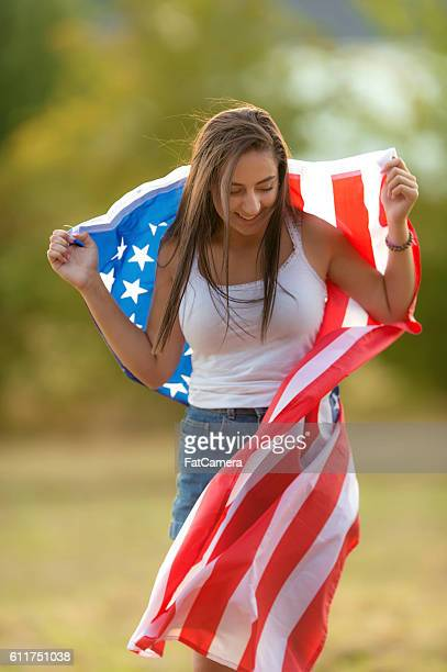 Teenage girl smiling and holding an American flag