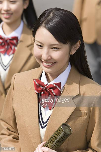Teenage girl smiling and holding diploma, high angle view, Japan