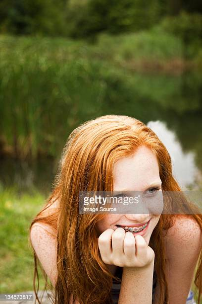 teenage girl smiling at friends with a lake behind her - jeune fille rousse photos et images de collection