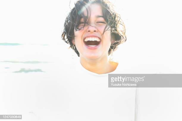 a teenage girl smiling at the sea - 喜び ストックフォトと画像