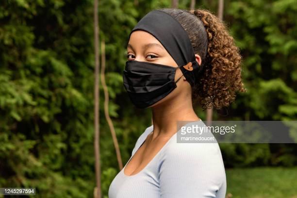 """teenage mädchen lächelnd behing stilvolle schutzmaske. - """"martine doucet"""" or martinedoucet stock-fotos und bilder"""