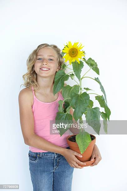 teenage girl,(13-14 years) smiling, holding sunflower, portrait - 14 15 years stock pictures, royalty-free photos & images